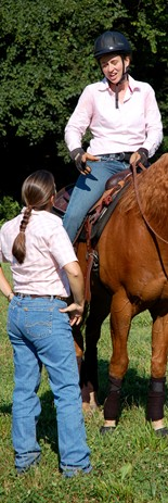 An instructor with her student in a western riding class.